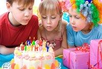 Два мальчика и девочка задувают свечи на праздничном торте