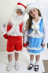 Девочка и мальчик в костюмах Деда Мороза и Снегурочки